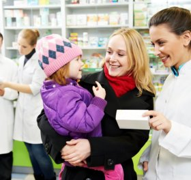 female pharmacist giving a medicine to a girl
