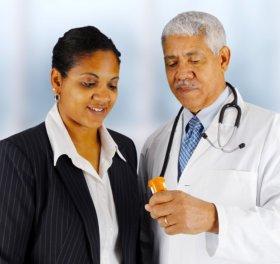 pharmacist giving prescription to a customer.